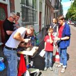 Letter 662: Michiel Deylius met sponsor en bezoekers bij het maken van de Letter